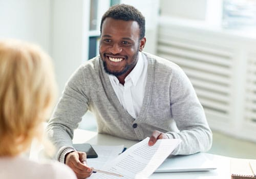 Man Smiling and holding paperwork
