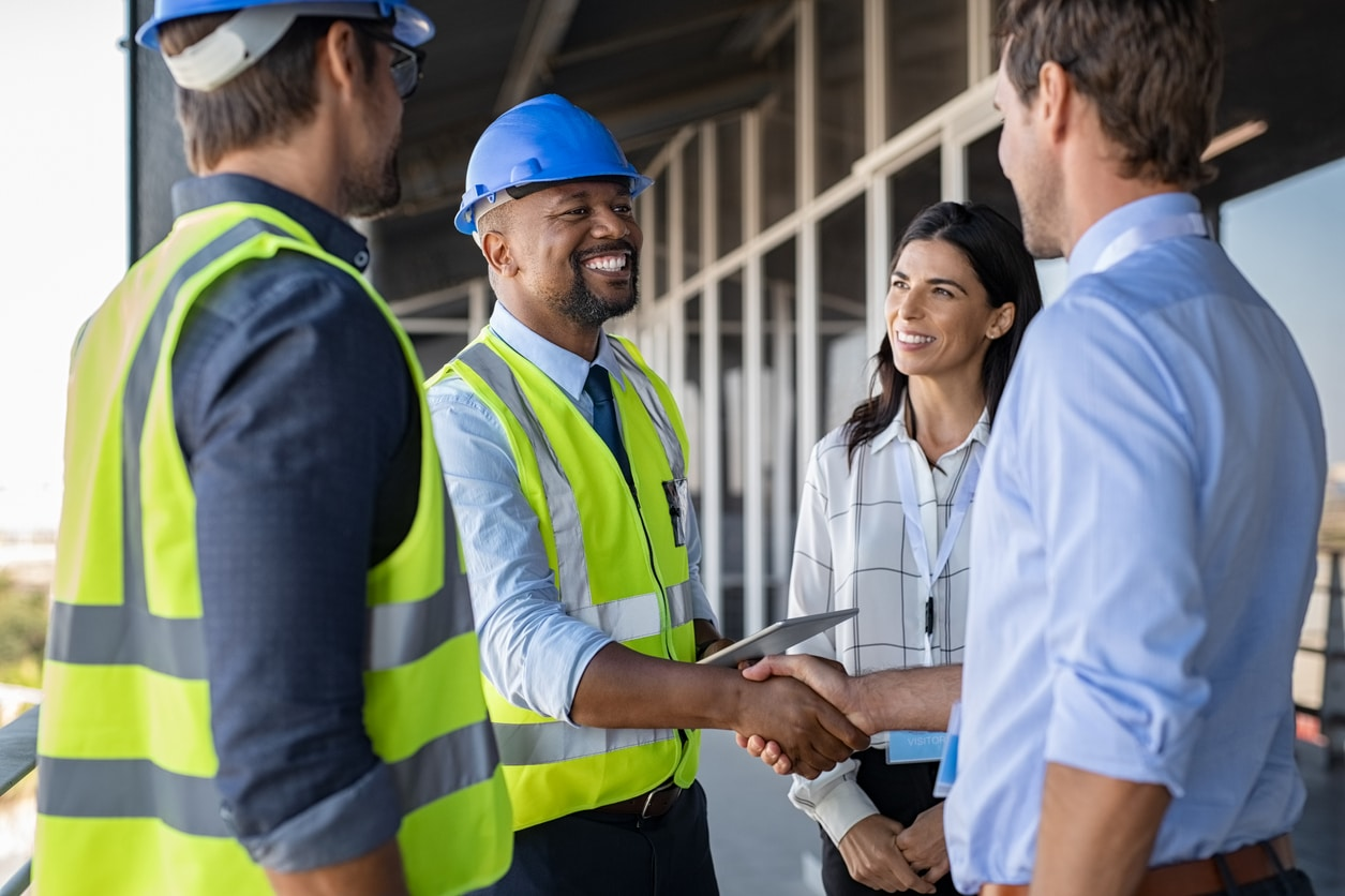 construction engineer in yellow vest shakes hand with man in blue shirt