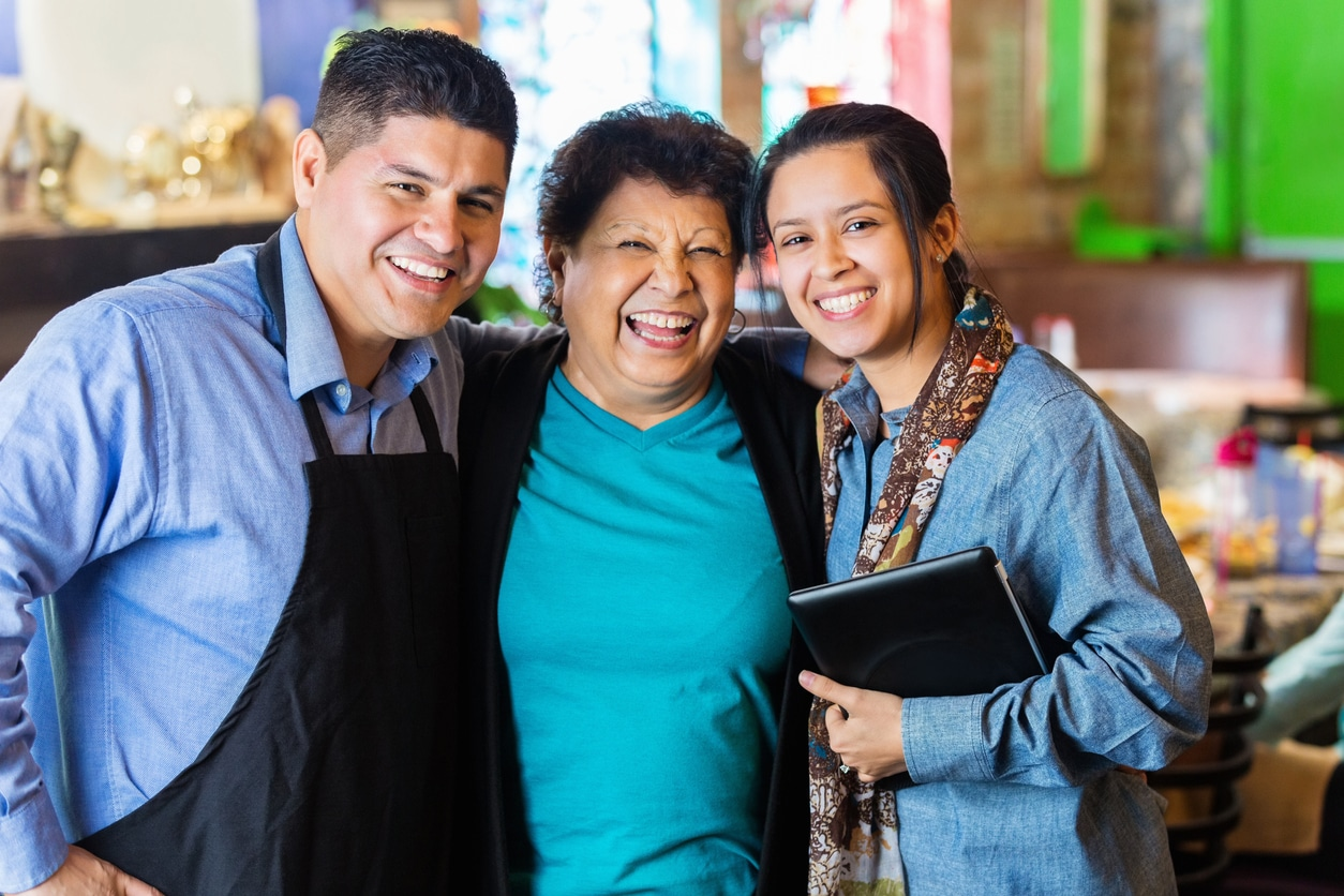smiling family with arms around each other amily at restaurant they own