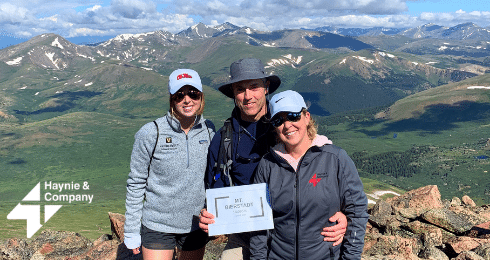 three people on mountain holding certificate