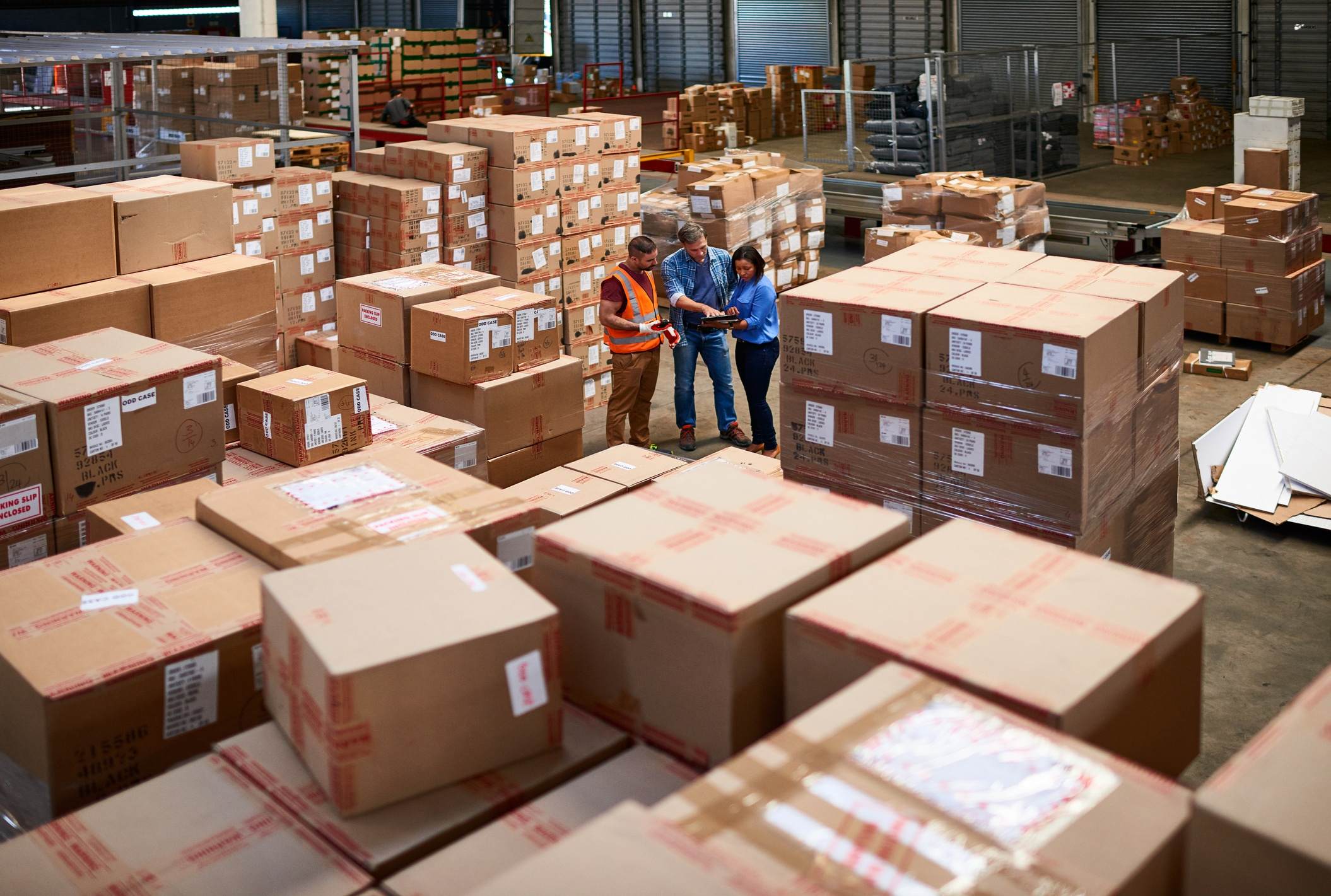 three people consulting in distribution warehouse