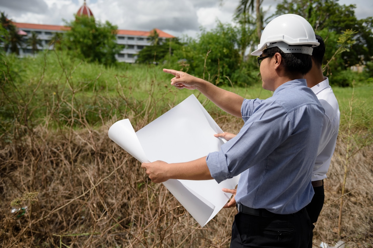 real estate developers looking at empty lot